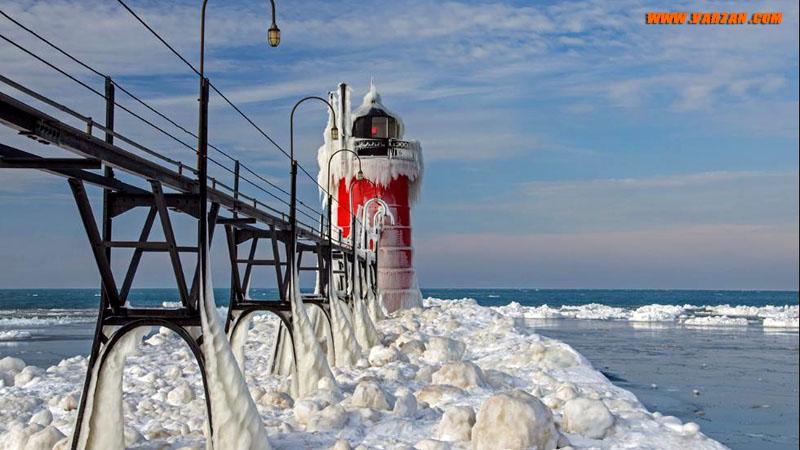 یخ اسکله و فانوس دریایی را در South Haven میشیگان پوشانده است. 17 ژانویه 2015