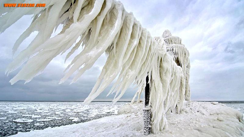 باد و موج های خروشان دیواری منحنی از یخ در بالای راه باریکی که به فانوس دریایی میشیگان ختم می شود، در 26 ژانویه 2013 ایجاد کرده اند.