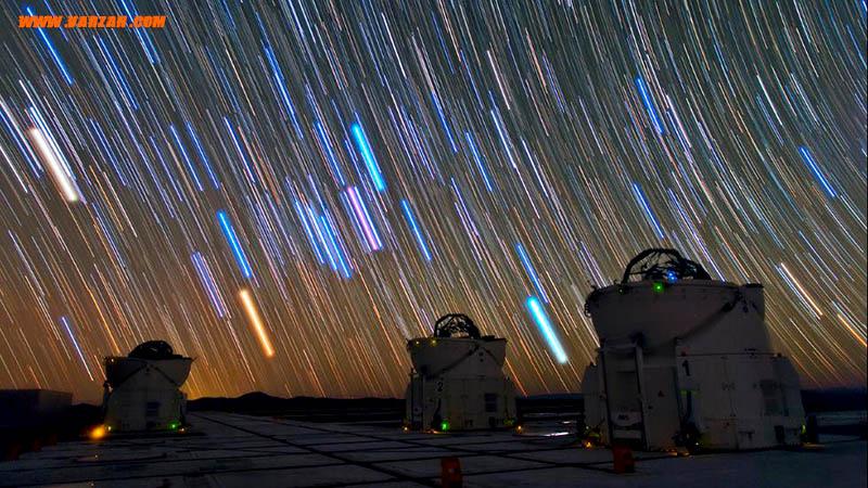 بالای سه تلسکوپ، نوارهای روشنایی طولانی در عرض آسمان شب