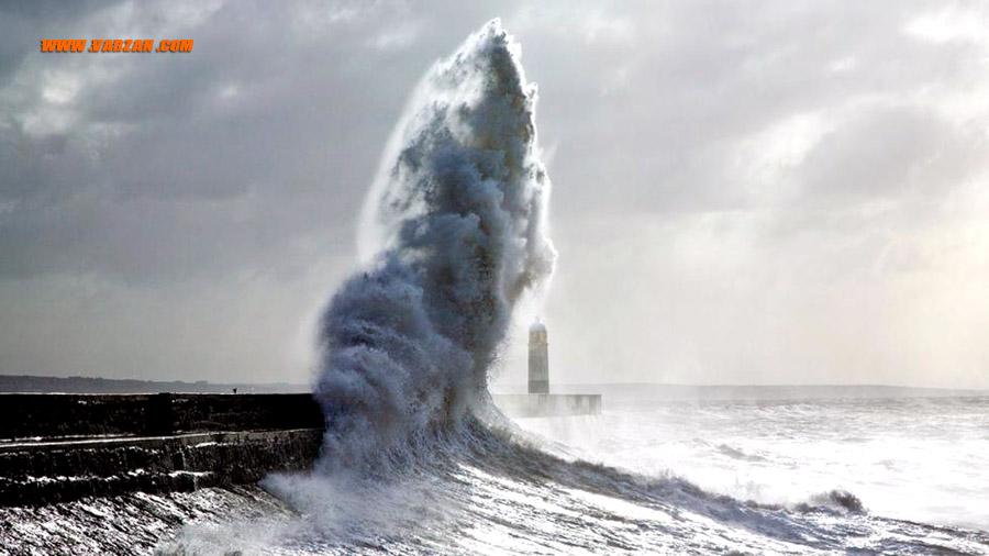 برخورد امواج خروشان به فانوس دریایی پورث کال در جنوب ولز در طول طوفان